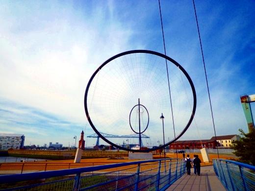 """球场旁边的雕塑,是两位艺术家赠送给俱乐部的。后面的蓝色大桥就是米堡的标志""""运输大桥"""",建于1911年"""